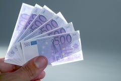 Die menschlichen Finger, die kleinen Euro anhalten, beachtet Bargeld Stockbilder