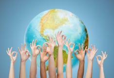 Die menschlichen Hände, die o.k. darstellen, unterzeichnen vorbei Erdkugel Lizenzfreies Stockbild