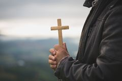Die menschlichen Hände, die ein Kreuz heilig halten und beteten für Segen vom Gott, Liebes-Anbetungs-Gottkonzept - Bild stockfotos