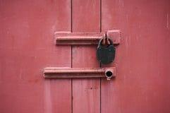 Die Metalltür ist- mit einem Vorhängeschloß rot Nahaufnahme Abstraktes backgro Stockbilder