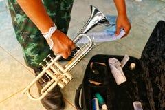 Die Militärhand hält das Instrument Trockenere Art der silbernen Trompete mit Flugschreiber auf dem Boden lizenzfreies stockfoto