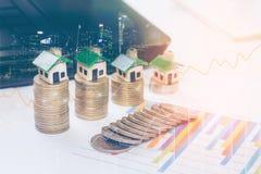 Die Miniaturhäuser, die auf Diagrammblattmünze stillstehen, stapelt Konzept für Eigentumsleiter, lizenzfreies stockbild