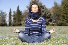 Die mittlere gealterte Frau, die Yoga tut, trainiert draußen Stockfotografie