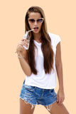 Die Modefrau, die stilvollen Blick trägt, trinkt Soda und wirft auf Farbhintergrund auf Lizenzfreies Stockfoto