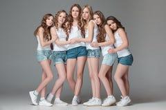 Die Modemädchen, die zusammen stehen und Kamera über grauem Studiohintergrund betrachten stockfotos