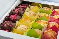 Die Muffins der unterschiedlichen Farbe verpackten in Papier Lizenzfreies Stockfoto
