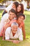 Die multi Generations-Familie, die herein liegt, häufen oben auf Gras zusammen an Lizenzfreie Stockbilder