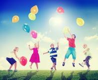 Die multiethnischen draußen spielenden Kinder steigt zusammen im Ballon auf Lizenzfreies Stockfoto