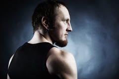 Die muskulöse Mannesrückseite auf schwarzem Hintergrund Lizenzfreies Stockfoto