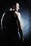 Die muskulöse Mannesrückseite auf schwarzem Hintergrund Stockbilder
