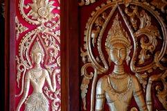 Die Muster geschnitzte künstlerische Schönheit des Türversprechens von Laos Lizenzfreie Stockbilder