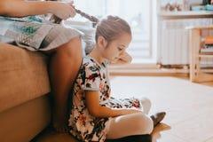 Die Mutter, die auf dem Sofa sitzt, flicht Haarsitzen ihrer Tochter auf dem Boden nahe bei ihr im gemütlichen hellen Raum lizenzfreie stockfotografie