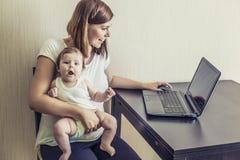 Die Mutter der Frau mit dem Kind auf Händen bei der Arbeit hinter t Stockfoto