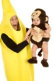 Die Mutter, die als Banane mit Affebaby gekleidet wird, halten heraus Stockfoto