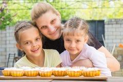 Die Mutter, die ihre Töchter umarmt, kochen köstliche kleine Kuchen Lizenzfreie Stockfotografie
