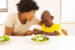 die Mutter, die Sohn fragt, essen Gemüse lizenzfreies stockbild