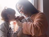 Die Mutter hält das neugeborene und trifft ihm mit ihrer älteren Schwester lizenzfreies stockfoto