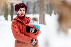 Die Mutter, die ihr Baby trägt, trägt rote Jacke und Riemen stockfotografie
