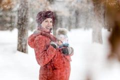 Die Mutter, die ihr Baby trägt, trägt rote Jacke und Riemen stockfoto