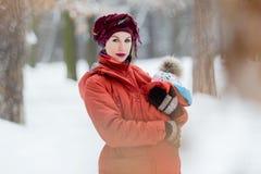 Die Mutter, die ihr Baby trägt, trägt rote Jacke und Riemen lizenzfreies stockbild