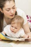 Die Mutter liest das Buch zum Baby. Lizenzfreies Stockfoto