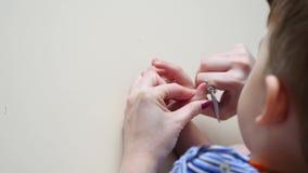 Die Mutter schnitt die Kind-` s Nägel mit Scheren ab Mutter kümmerte sich um den Händen ihres kleinen Jungen Nahaufnahme stock video