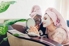 Die Mutter und ihre erwachsene Tochter, die Spiegel mit Gesichtsmasken betrachten, trafen zu Frauen, die Spaß kühlen und haben lizenzfreies stockfoto