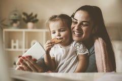 Die Mutter und kleines Mädchen, die Selbst nehmen, stellen zu Hause dar lizenzfreie stockfotos