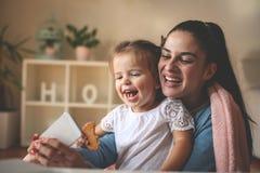 Die Mutter und kleines Mädchen, die Selbst nehmen, stellen zu Hause dar abschluß lizenzfreie stockfotografie