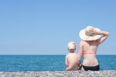 Die Mutter und Sohn, die auf dem Strand sitzen und bewundern das Meer Ansicht von der Rückseite Lizenzfreie Stockbilder