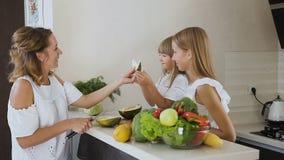 Die Mutter und Töchter, die schneiden und essen grüne Melone auf der Küchenarbeitsfläche zu Hause Frau schneidet eine Melone und  stock video
