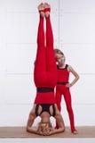 Die Mutter und Tochter, die Yoga tut, trainieren, Eignung, die Turnhalle, welche die gleichen bequemen Trainingsanzüge, zusammeng Stockfotografie