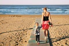 Die Mutter und Tochter, die durch hölzernen Bodenbelag auf Sand gehen, setzen an der Küste auf den Strand Sommerfamilienurlaub Ki Lizenzfreie Stockfotografie