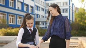 Die Mutter und Tochter jugendlich sind, stehen au?erhalb des Colleges nach Klasse in Verbindung stock video footage