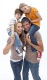 Die Mutter und Vater, die Kinder geben, tragen Fahrt huckepack stockbild
