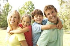 Die Mutter und Vater, die Kinder geben, tragen huckepack Stockbilder