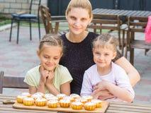 Die Mutter und zwei Töchter, die bei Tisch sitzen auf, welchen legen, kochten sie Ostern-kleine Kuchen Stockbild