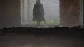 Die mysteriöse Zahl eines Mannes in einem schwarzen Mantel ist auf einem staubigen Raum in Richtung der Kamera stock video footage