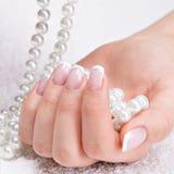 Die Nägel der Schönheit mit französischer Maniküre und Perlen stockfotografie
