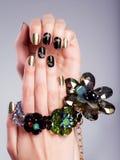 Die Nägel der Schönheit mit kreativer Maniküre und Schmuck lizenzfreie stockfotos