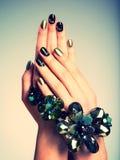 Die Nägel der Schönheit mit kreativer Maniküre und Schmuck stockbild