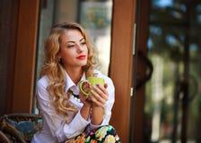 Die nachdenkliche Frau, die mit Kaffeetasse sitzt und hat einen Rest stockfotografie
