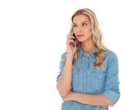 Die nachdenkliche Frau, die am Telefon spricht, schaut oben, um mit Seiten zu versehen Stockbilder