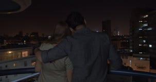 Die Nachtstadt betrachten, die in den Umarmungen des liebevollen Mannes ist stock footage