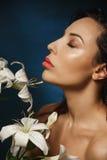 Die nackte dünne Frau, die mit Augen aufwirft, schloss und hielt Lilienblumen Stockbild