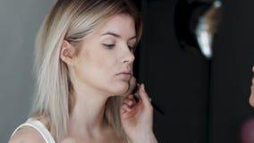 Die Nahaufnahme der Frau Kosmetik mit einem großen auftragend bilden Bürste Mädchen im Salon richten her, wenden Pulver auf der H stock video footage