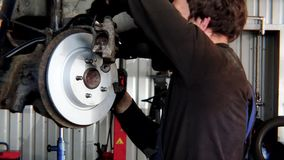Die Nahaufnahme des Arbeitskraftmannes neue Bremsscheibe am alten Auto anbringend hob in Reparaturwerkstatt an stock video