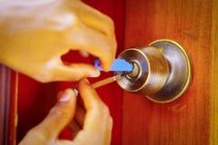 Die Nahaufnahmehände des Bauschlossers Metall verwendend wählen Werkzeuge aus, um verschlossene Tür zu öffnen stockbild