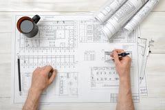 Die Nahaufnahmehände des Mannes einen Technikteiler über Zeichnung halten planen in der Draufsicht Stockfoto