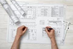 Die Nahaufnahmehände des Mannes einen Technikteiler über Zeichnung halten planen in der Draufsicht Lizenzfreie Stockbilder